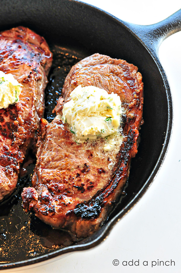 Skillet Steaks with Gorgonzola Herbed Butter - Nothing beats the sear of a steak cooked in a cast iron skillet! Topped with Gorgonzola Herbed Butter? Makes this skillet steak recipe out of this world! // addapinch.com