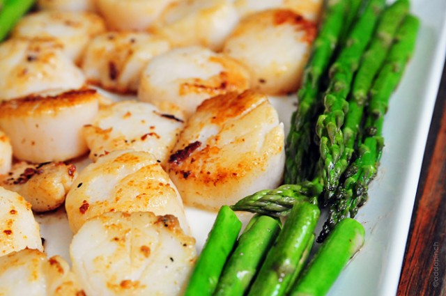Horizontal photograph of cooked scallops and asparagus on a white plate. // addapinch.com