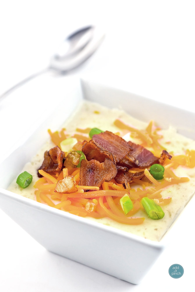 Loaded baked potato soup makes a warm, comforting potato soup recipe. Made with baked potatoes blended into a creamy soup and topped with your potato bar favorites! // addapinch.com