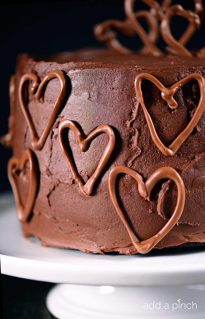 Celebration Chocolate Cake Recipe made with whipped mocha ganache filling and dark chocolate buttercream frosting! It is perfect for a party! // addapinch.com