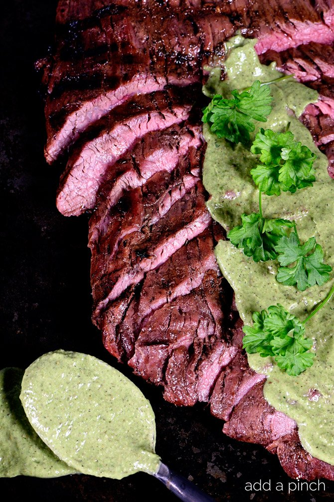 Grilled Flank Steak sliced and served with a chimichurri sauce. // addapinch.com