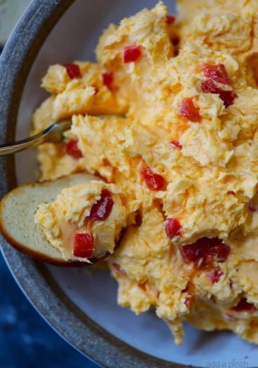 Southern Pimento Cheese Recipe - A staple spread in Southern home and parties, pimento cheese is a classic! Made with cheddar cheese, pimentos and a secret ingredient, this pimento cheese recipe is always a hit! // addapinch.com