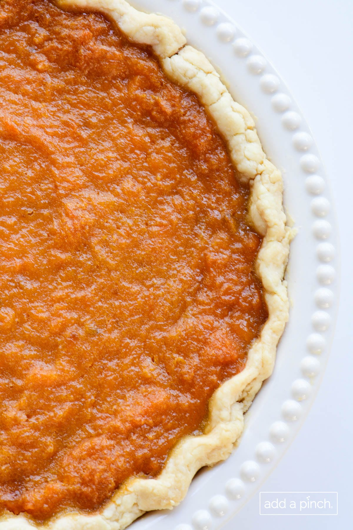 Overhead photograph of sweet potato pie in a homemade pie crust in white pie plate.