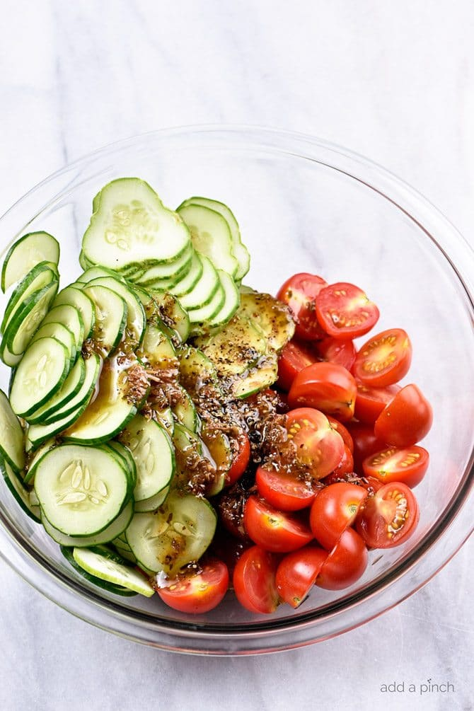 Cucumber Tomato Salad Recipe - A quick and easy summer staple, this cucumber and tomato salad goes well with fish, chicken, pork, or a plate filled with veggies! Add in onions too if you like! // addapinch.com