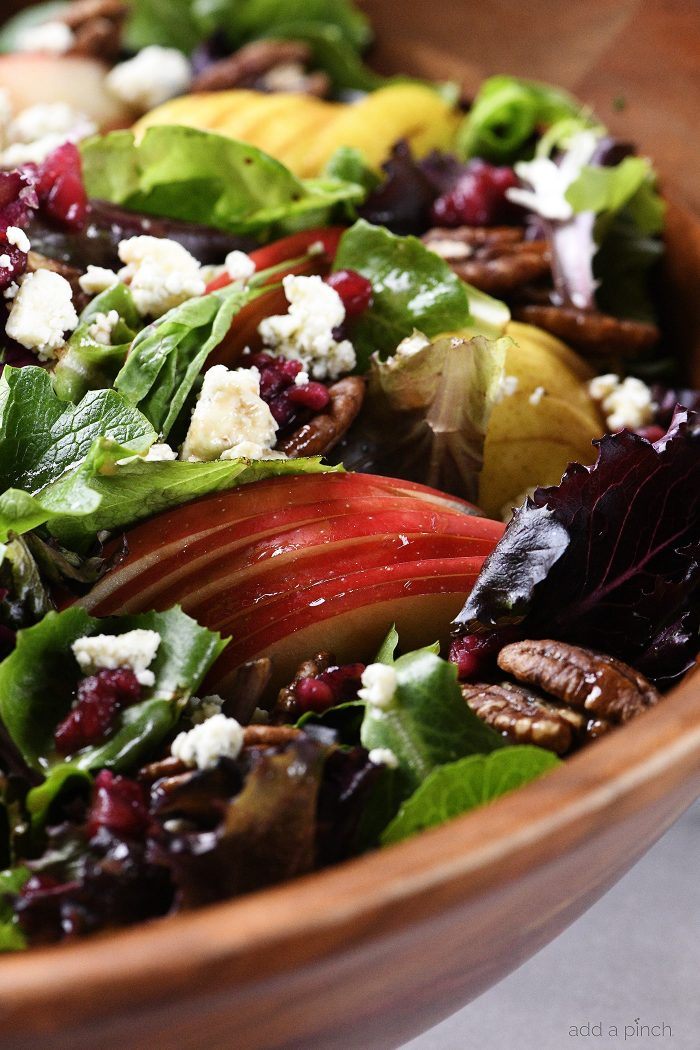 Apple Pear Salad with Pomegranate Vinaigrette in a wooden salad bowl addapinch.com
