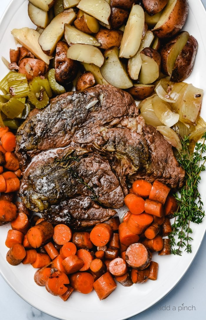 Photograph of cooked roast surrounded by potatoes, onions, fresh thyme, and carrots on a white platter. // addapinch.com