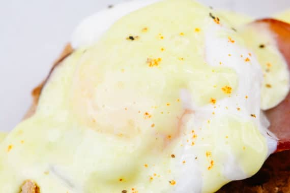 Eggs Benedict Recipe - Toasted English muffins topped with ham, bacon, or Canadian-style bacon, and poached eggs and then drizzled with hollandaise sauce make this a favorite brunch recipe. // addapinch.com