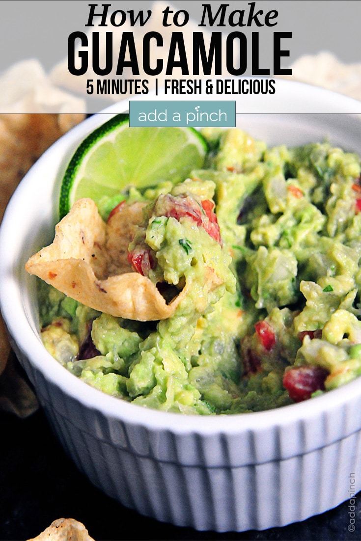 Fresh Guacamole with chip and a lime slice in a white bowl - with text - addapinch.com
