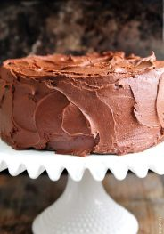 Amazing chocolate cake photographed with rich chocolate buttercream frosting on a white cake stand // addapinch.com
