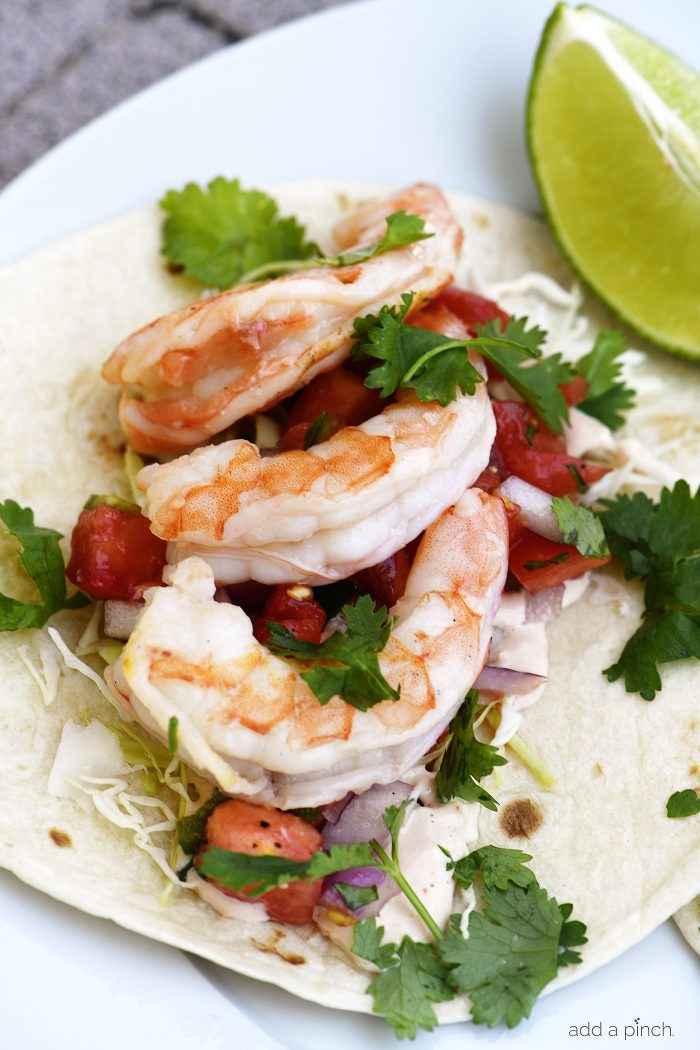 Shrimp Tacos Recipe - These quick and easy shrimp tacos are always a favorite. Made with delicious, tender grilled shrimp for a spicy, perfect shrimp taco! // addapinch.com