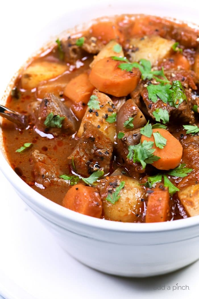 Photograph of homemade beef stew in a white bowl on a white background. // addapinch.com
