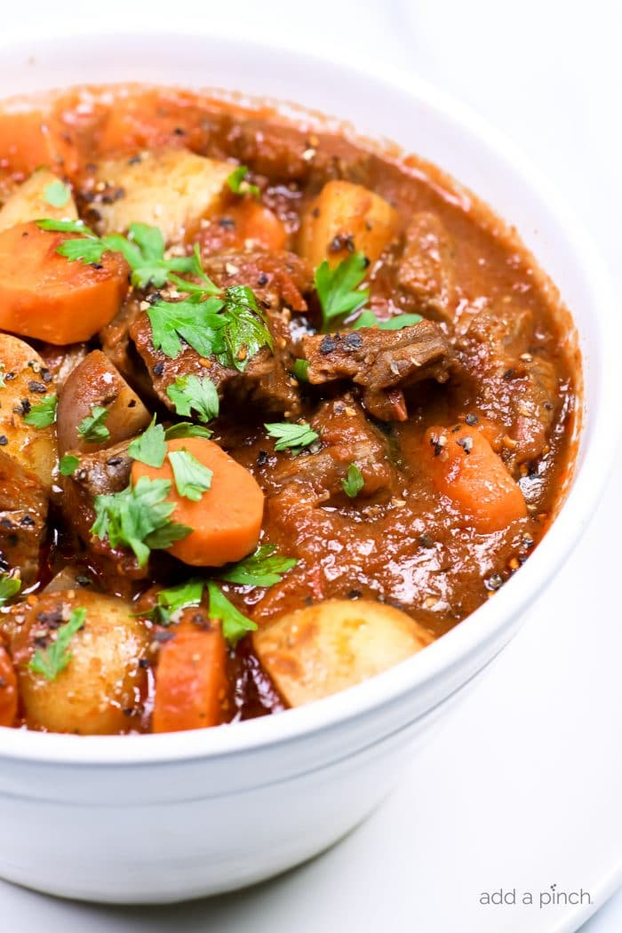 Closeup photograph of beef stew in a white bowl on a white counter. // addapinch.com