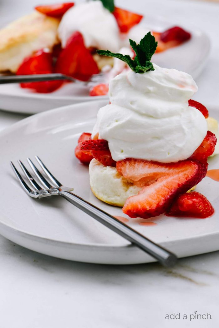 Strawberry Shortcake makes a classic dessert. Made of tender biscuits, topped with sweetened strawberries, and whipped cream, this simple strawberry shortcake is a favorite! // addapinch.com