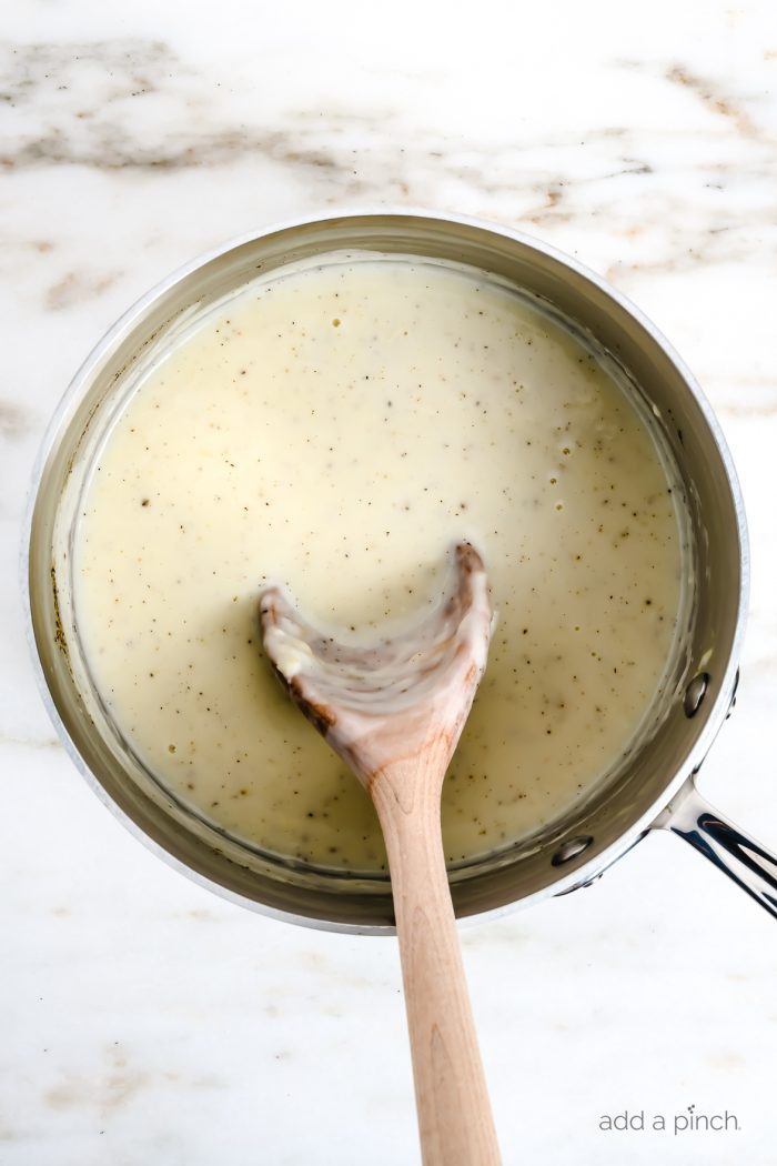 Condensed cream of chicken soup in a saucepan with a wooden spoon. // addapinch.com
