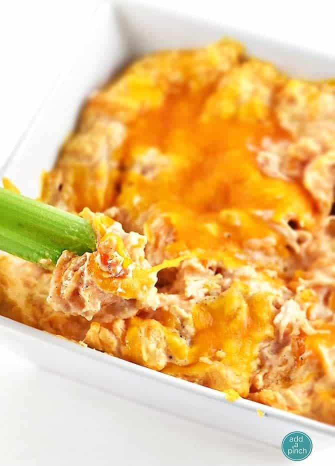 Buffalo Chicken Dip tastes like the buffalo chicken wings we love but without the mess! This easy appetizer is made with just a handful of ingredients in the oven or slow cooker! // addapinch.com