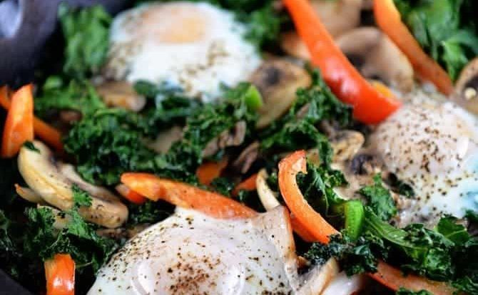 This kale breakfast skillet recipe is packed with flavor and ready in minutes! Made with kale, mushrooms, onions, peppers, and topped with eggs. // addapinch.com