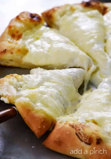 A simple recipe for homemade three cheese pizza that takes ordinary cheese pizza to a whole new level! // addapinch.com