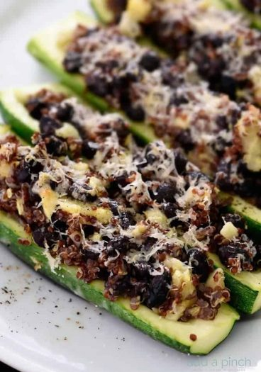 This stuffed zucchini recipe is a delicious dish made of zucchini stuffed with a mixture of black beans, quinoa, zucchini and topped with parmesan. It is definitely a filling favorite! // addapinch.com