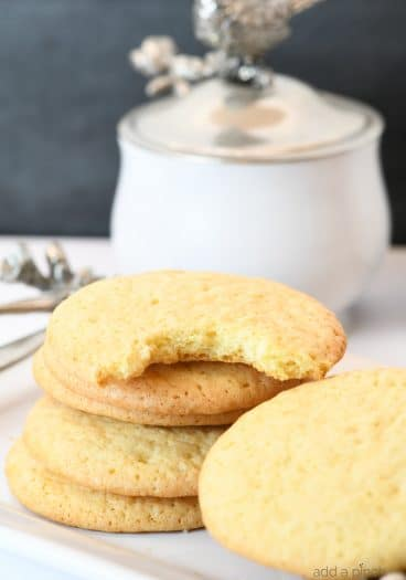 Photograph of stack of teacake cookies on a white platter. // addapinch.com