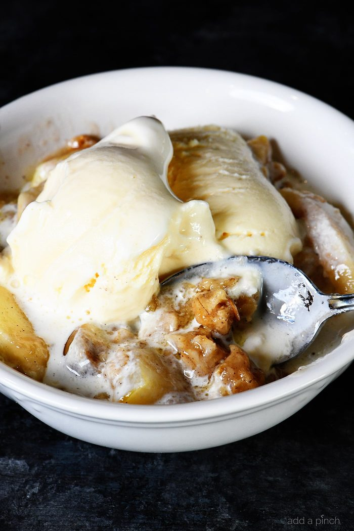 Bowl of Apple Crisp topped with vanilla ice cream - from addapinch.com