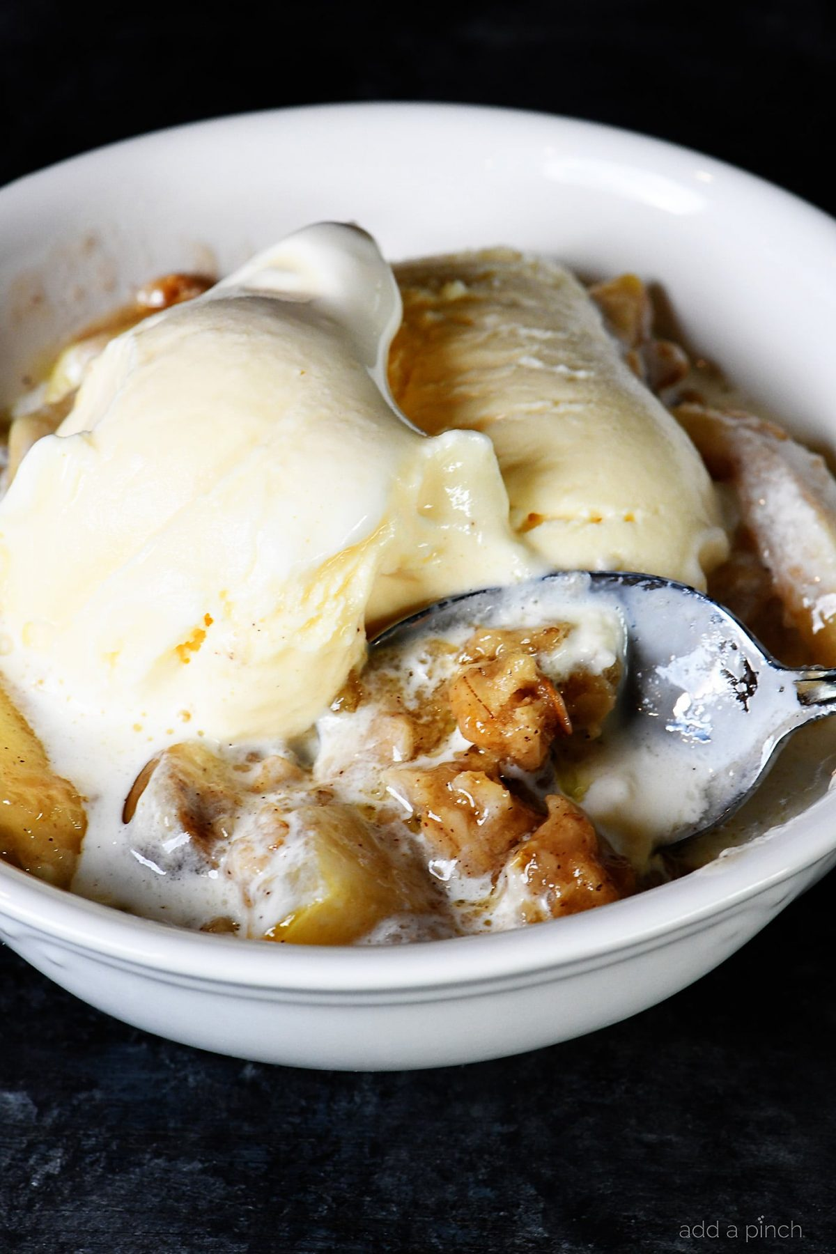 photograph of dessert with vanilla ice cream in a white bowl.