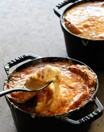French Onion Soup makes a comforting, classic bowl of soup! Made with caramelized onions a slice of crusty bread and melty, delicious cheese! Includes stovetop and slow cooker methods! // addapinch.com