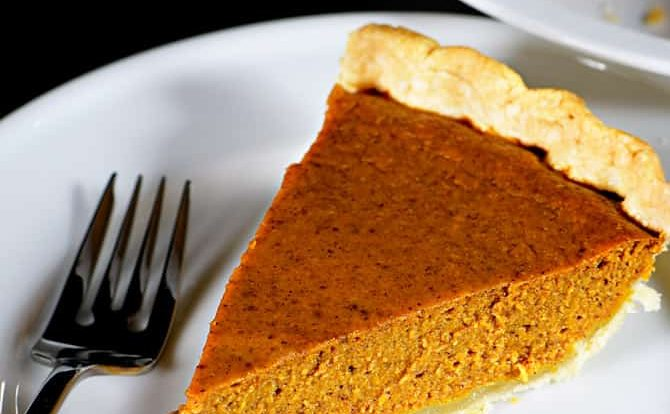 photograph of slice of pumpkin pie on a white plate.