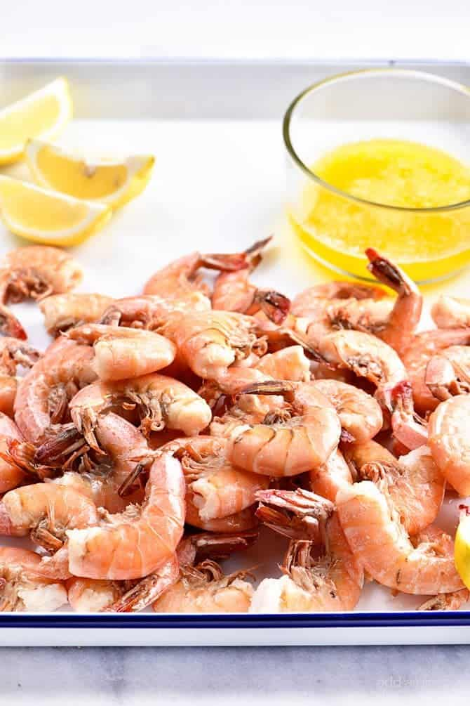 Boiled Shrimp piled on a white platter, along with lemon wedges and drawn butter // addapinch.com