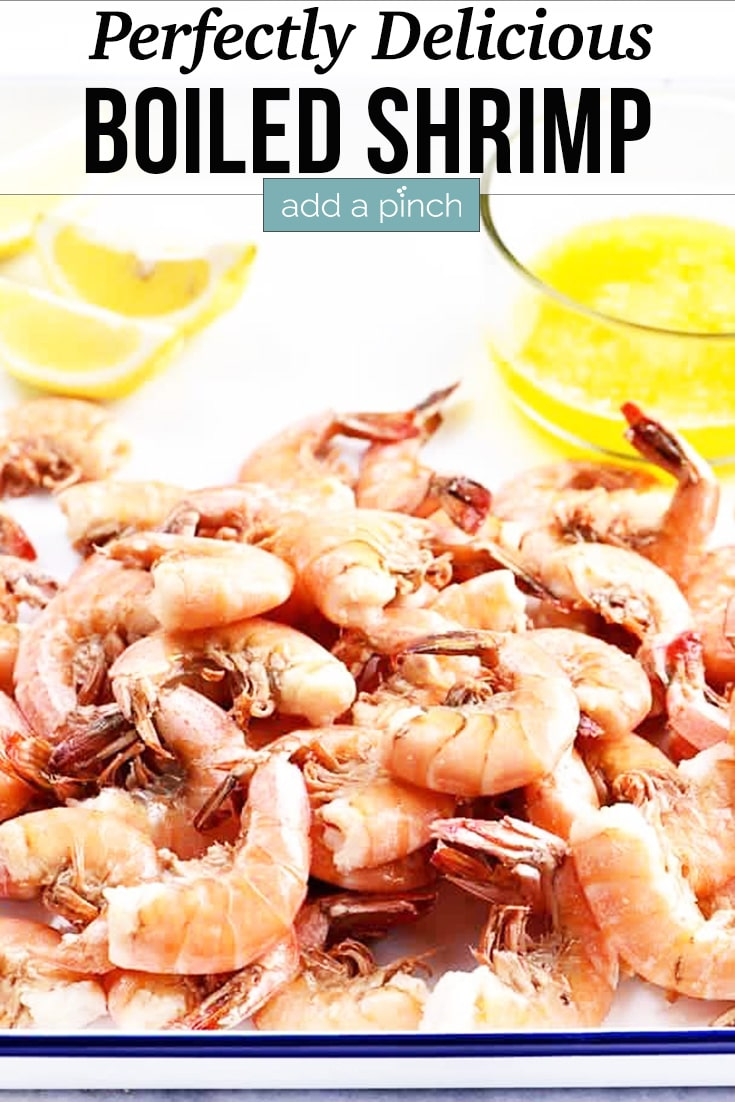 Boiled Shrimp with lemon slices and drawn butter on a white enamel serving tray - with text - addapinch.com