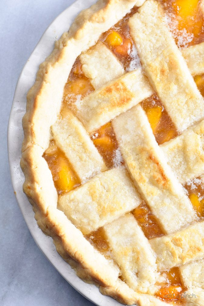 Classic Peach Pie Recipe - This Classic Peach Pie Recipe is a summer staple! Made with a lattice-topped double crust and filled with delicious peaches! // addapinch.com