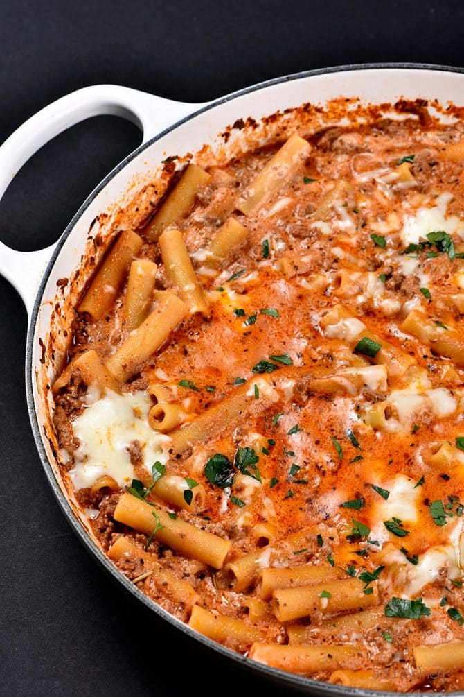 Skillet Beef Ziti in skillet topped with melted cheese and herbs - addapinch.com