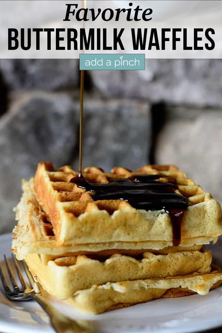Stack of Our Favorite Buttermilk Waffles being drizzled with syrup - with text - addapinch.com