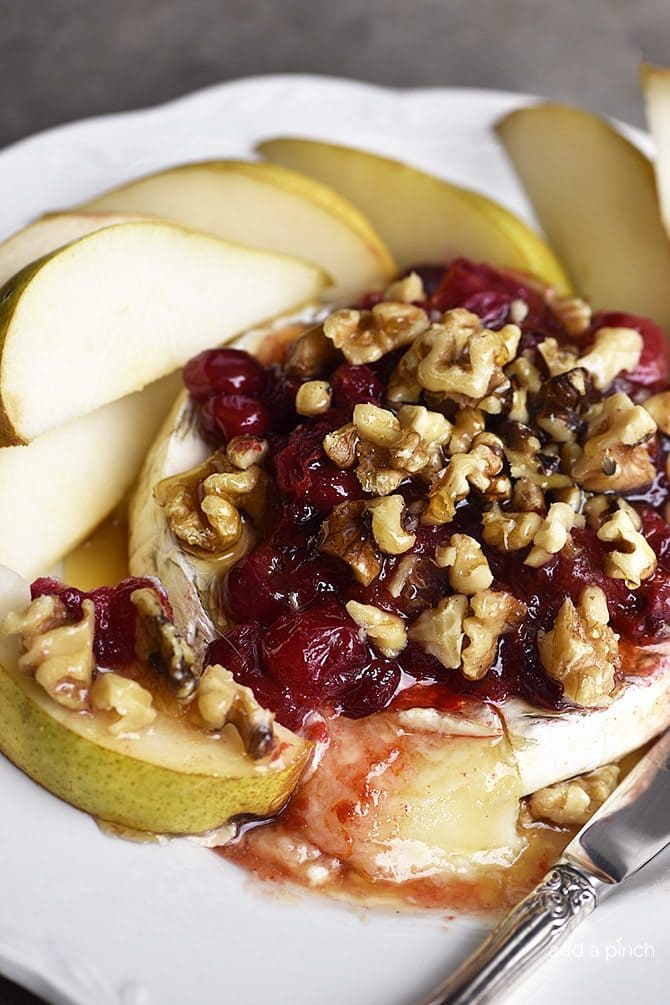 Warm Brie with Honeyed Fruit Compote makes a beautiful, quick and easy appetizer. Made with a honeyed cranberry walnut fruit compote, this warm brie recipe is festive for the holidays! // addapinch.com