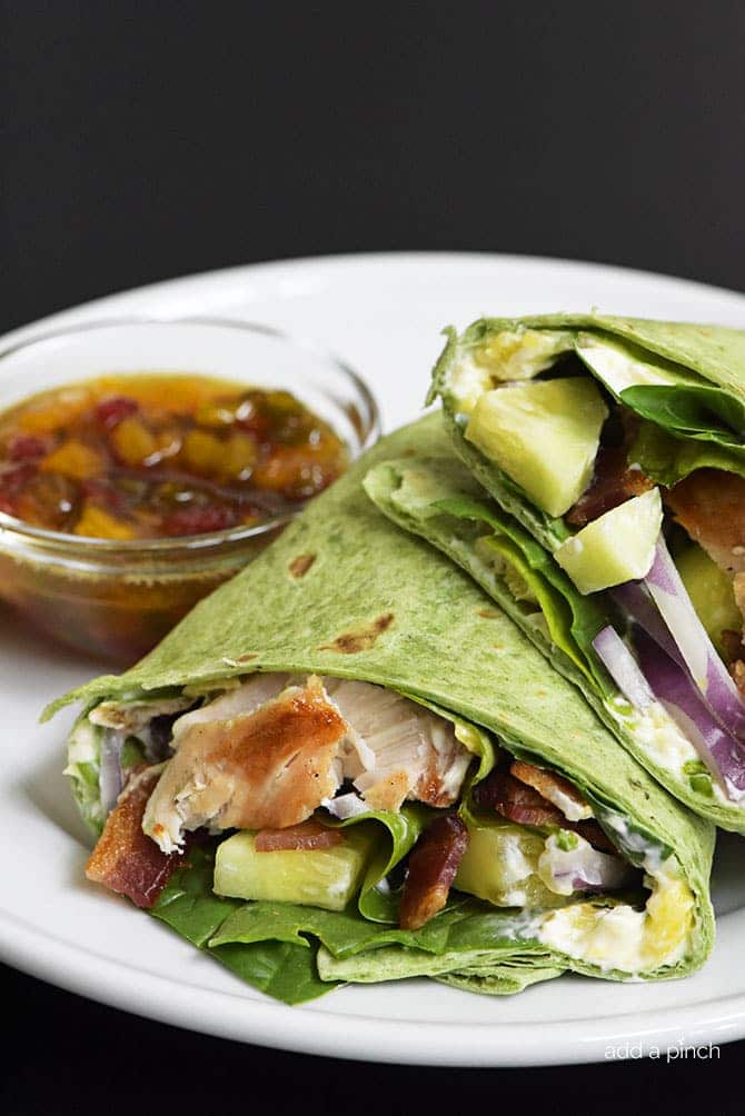 Sweet and Spicy Chicken Wraps - Quick, easy and oh so delicious! This chicken wraps recipe is made with chicken, bacon, cucumbers, red onions, and a special sweet and spicy spread! // addapinch.com