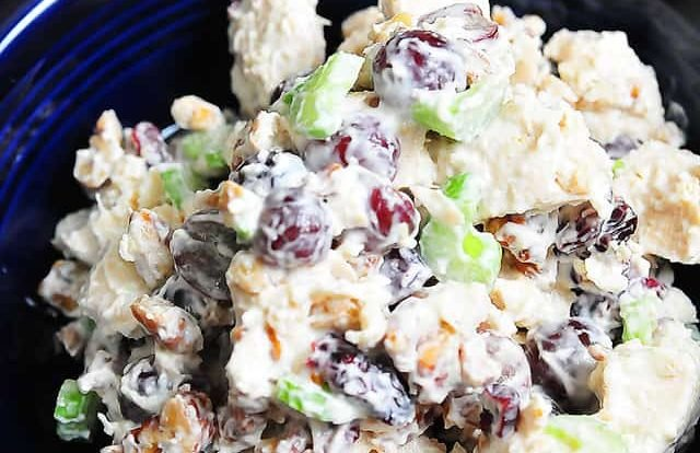 Photograph of chicken salad in a blue bowl on a dark counter.