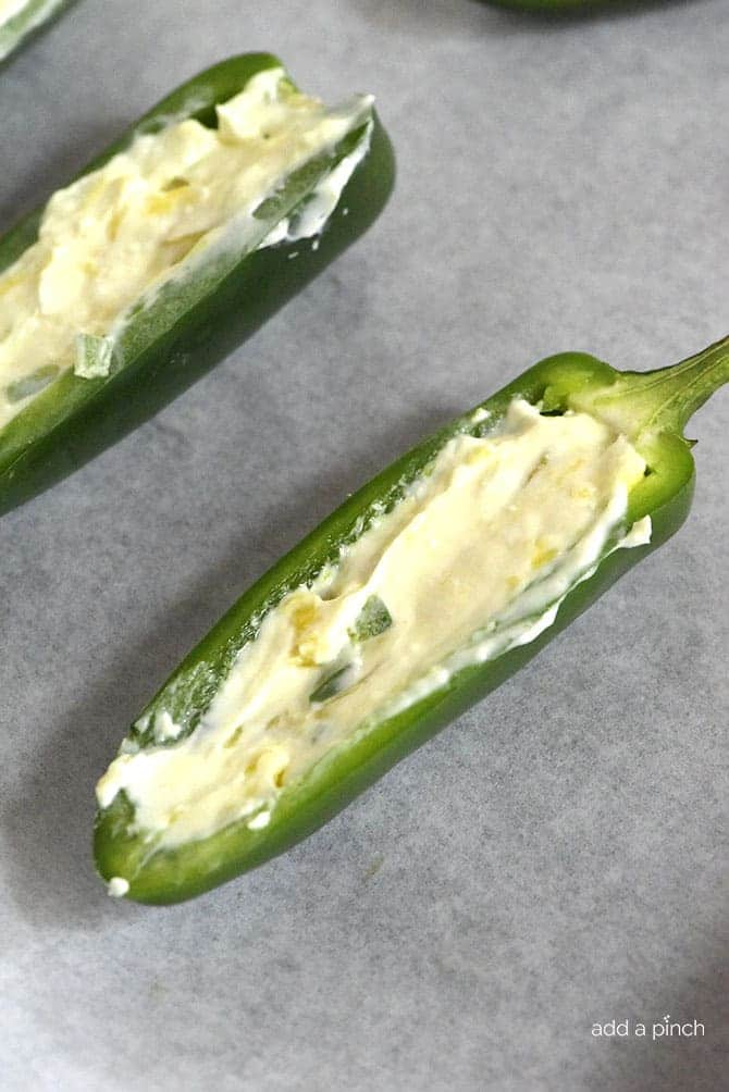 Pineapple Jalapeno Popper Recipe - Sweet and spicy, these jalapeno poppers are made with a pineapple cream cheese spread, wrapped with bacon and baked to perfection! // addapinch.com