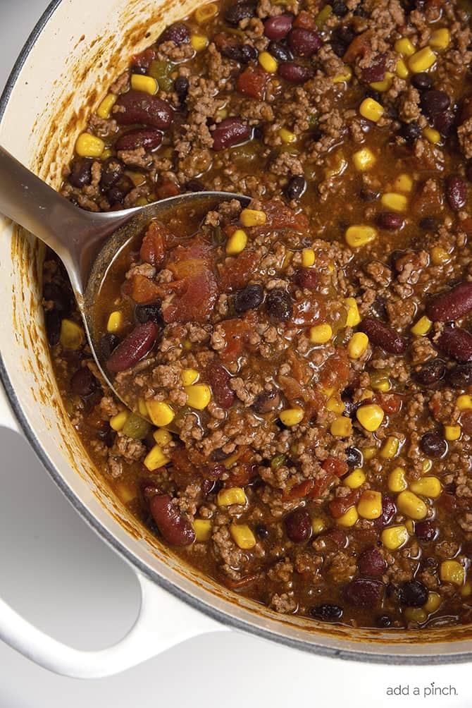Ladle filled with meaty soup in a white Dutch oven with ground beef, corn, and beans