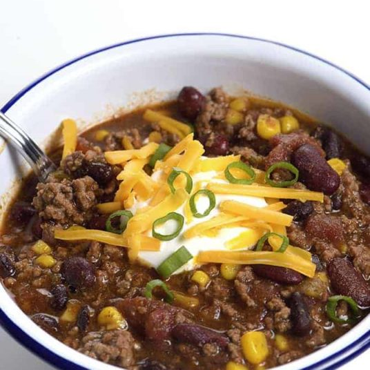 Taco Soup in a white bowl topped with sour cream, cheese, and green onions. #tacosoup #kidfriendly