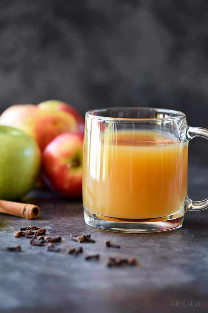 Homemade Apple Cider in glass mug surrounded by fresh apples and spices // addapinch.com