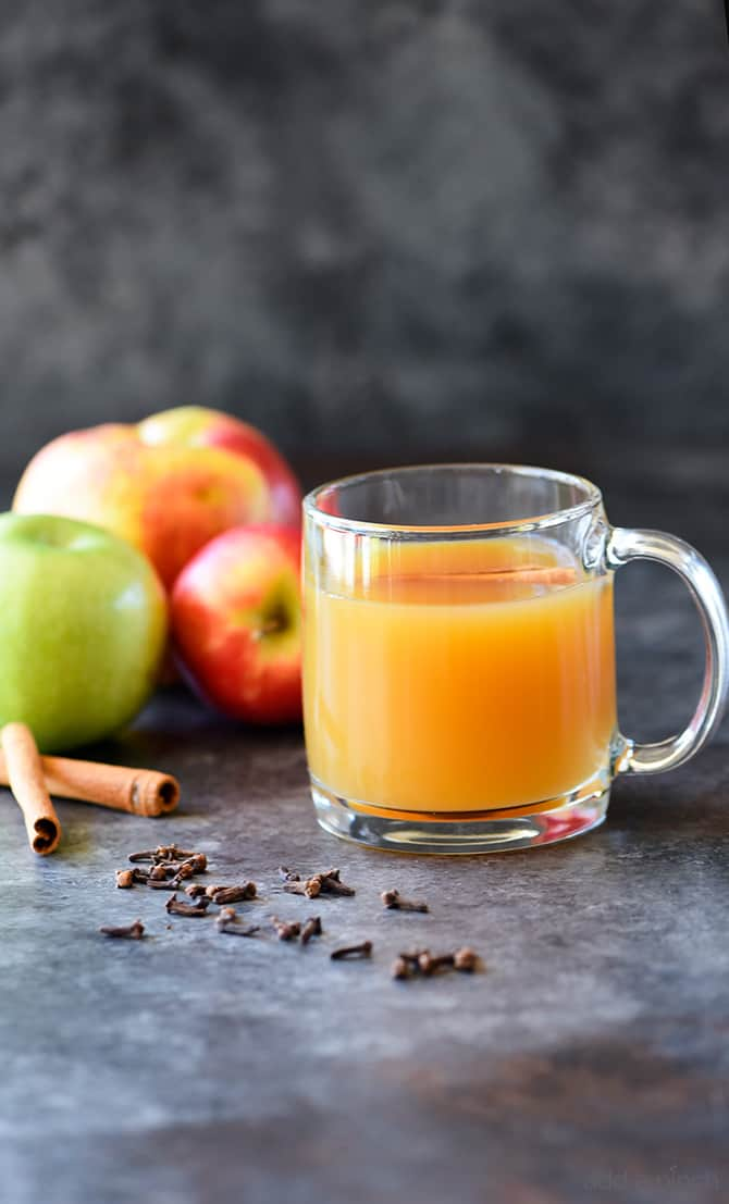 Homemade Apple Cider in glass mug surrounded by cinnamon sticks, cloves and apples // addapinch.com