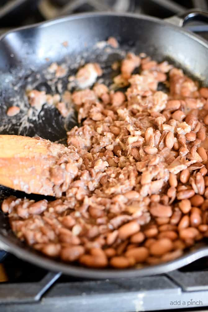 Refried Beans Recipe - This quick and easy refried beans recipe made with pinto beans, onion, and spices makes a delicious side dish for so many meals! // addapinch.com