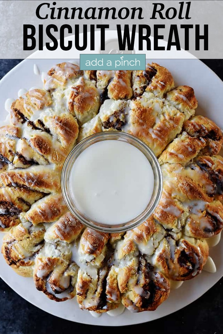 Cinnamon Roll Biscuit Wreath with icing in the middle of wreath - with text - addapinch.com