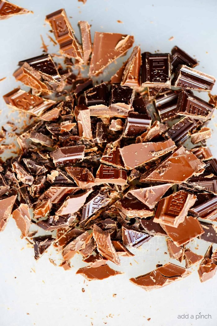 Photograph of chopped Hershey's chocolate bars on a white background. // addapinch.com