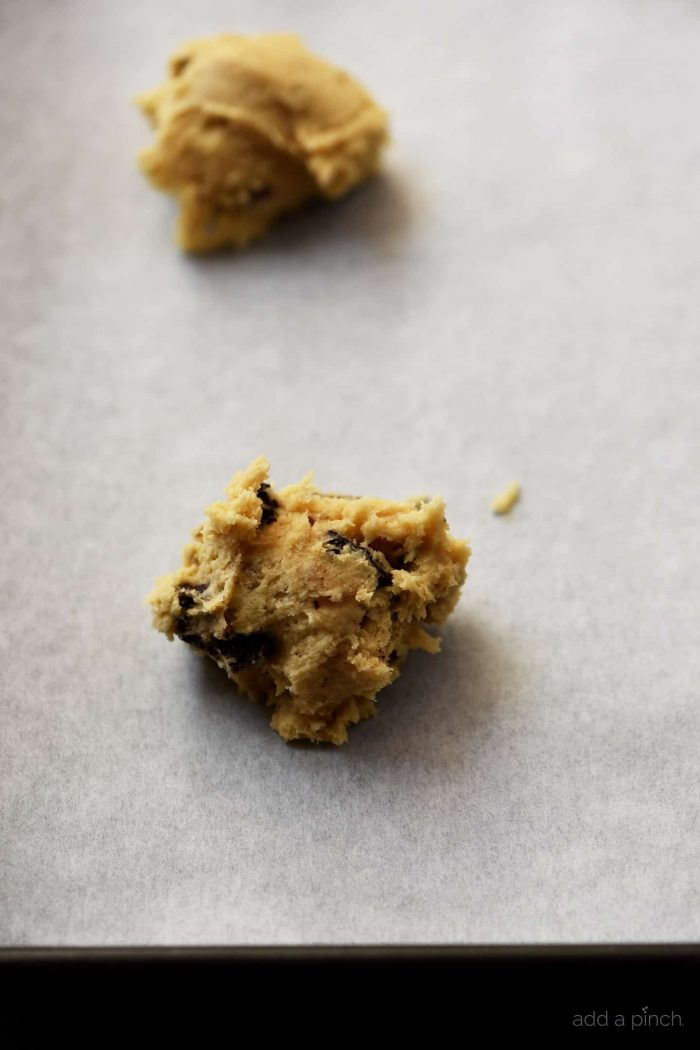 Photograph of chocolate chip cookie dough on a parchment lined baking sheet.// addapinch.com
