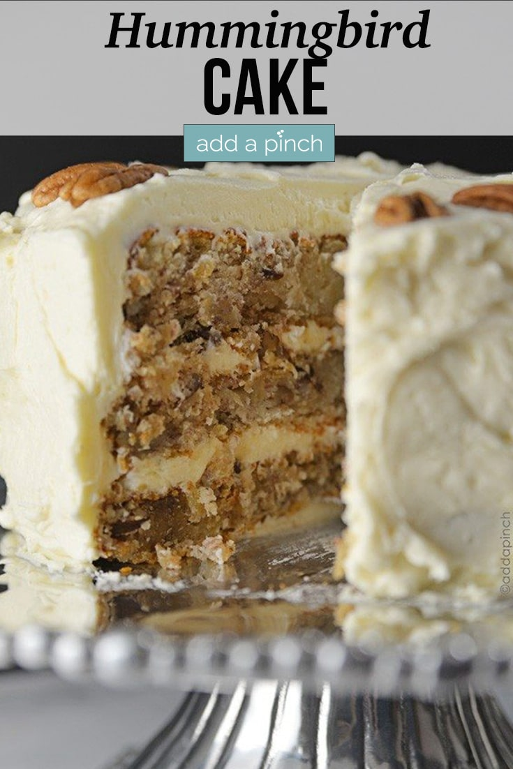 Sliced Hummingbird Cake topped with pecan halves served on pewter cake stand - with text - addapinch.com