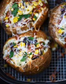 Air Fryer Enchilada Stuffed Baked Potatoes Recipe - This quick and easy recipe combines a perfect baked potato filled with black beans, enchilada sauce, and more! // addapinch.com
