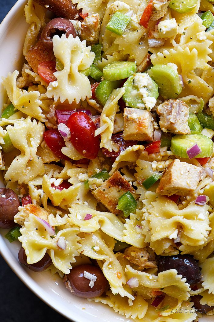 Greek Chicken Pasta Salad Recipe - This easy pasta salad recipe is so easy and delicious! Made with grilled chicken, pasta, an assortment of vegetables and topped with feta cheese and a delicious Greek dressing! // addapinch.com