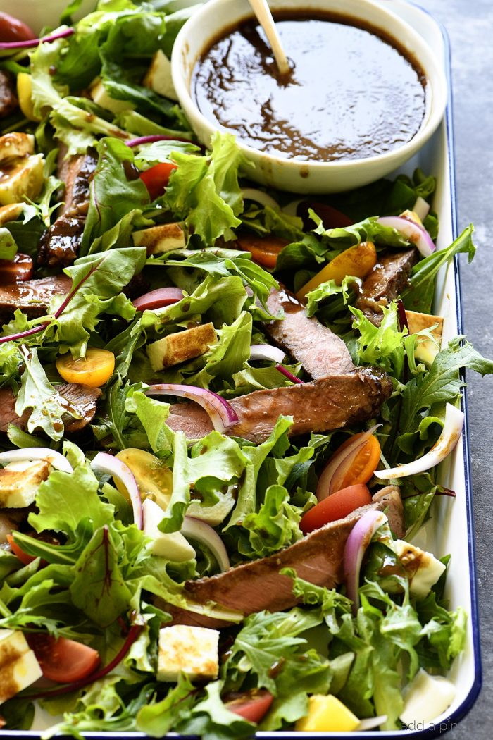 Balsamic Steak Salad Recipe - A hearty balsamic steak salad recipe is served with lots fresh vegetables, mozzarella, fresh basil and a Homemade Balsamic Vinaigrette. // addapinch.com