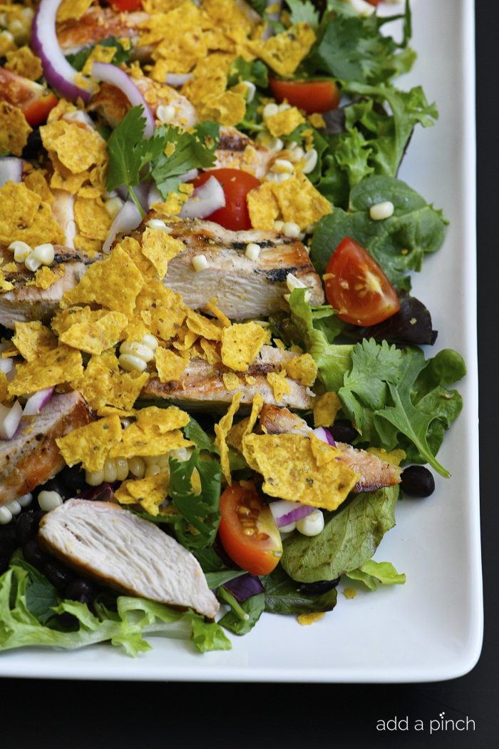 Grilled Chicken Fiesta Salad Recipe - This simple grilled chicken salad recipe is kicked up a notch for a spicy Tex-Mex favorite! // addapinch.com