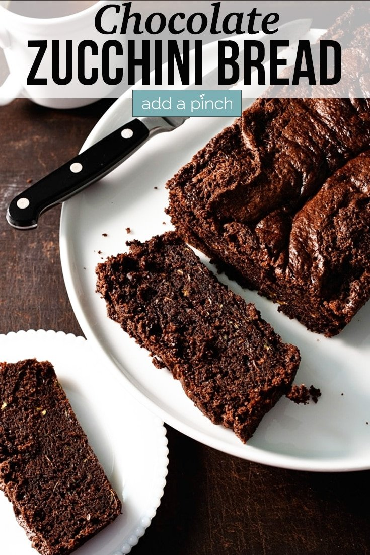 Chocolate Zucchini Bread on white platter with two pieces sliced off beside cup of coffee - with text - addapinch.com